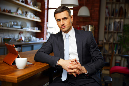 man coffee: Confident businessman in formal cloths drinking coffee and reading news in the kitchen Stock Photo