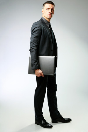 Full-length portrait of a businessman standing with laptop over gray background photo
