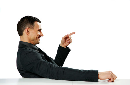 Businessman sitting at the table and pointing at copyspace photo