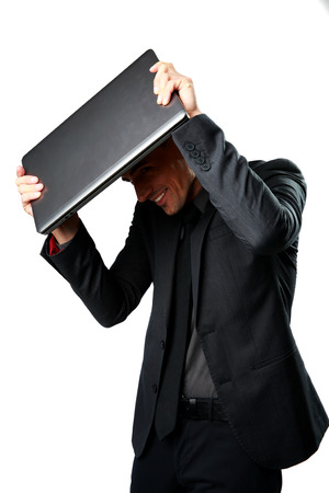 hides: Business man hides under the laptop in his hands