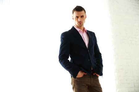 Confident fashion man standing over white