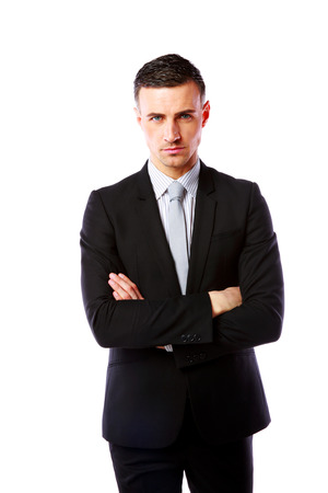 Handsome businessman standing with arms folded over white  photo