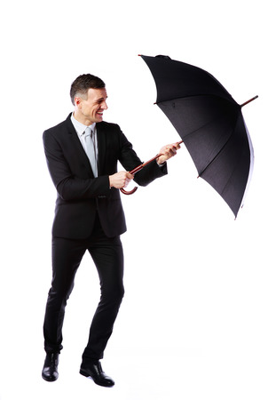 Businessman having fun with umbrella isolated on a white background photo