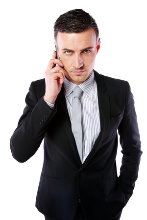 impassive: Business man talking on his mobile phone over white background