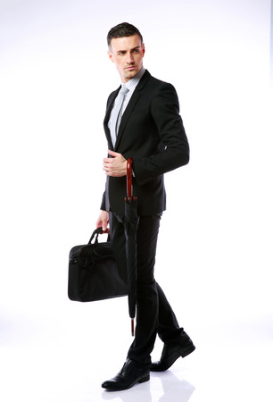 Full-length portrait of a confident businessman standing with umbrella and laptop bag photo