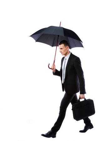 Businessman walking with umbrella and laptop bag on gray background photo