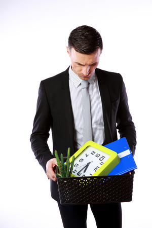 You are fired! Businessman hold box with personal belongings on gray background Stock Photo