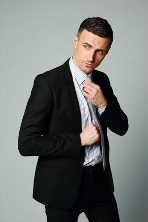 Handsome businessman straightening his tie on gray background photo