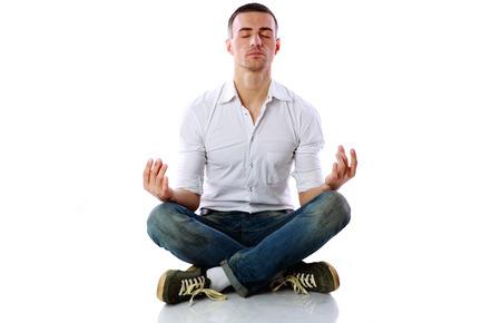 dhyana: L'uomo in panno casual seduto nella posizione del loto su sfondo bianco Archivio Fotografico