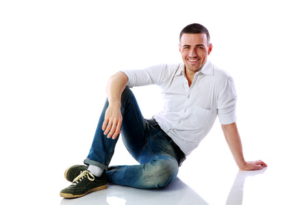 Happy man sitting at the floor over white background photo