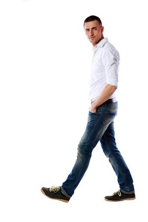 bonhomme blanc: Vue lat�rale portrait d'un homme d�contract� marchant sur fond blanc Banque d'images