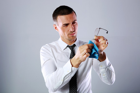 Handsome businessman wiping eyeglasses with rag on gray background photo