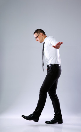 duality: Businessman walking on invisible rope on gray background Stock Photo