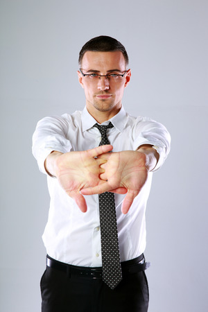 tiring: Businessman stretching after a tiring work on gray background Stock Photo