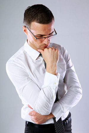 dissapointed: Portrait of a thoughtful businessman in glasses on gray background