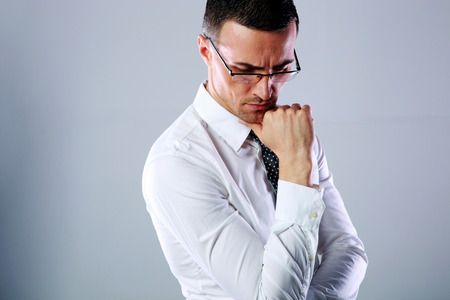 dissapointed: Portrait of a pensive man in glasses on gray background