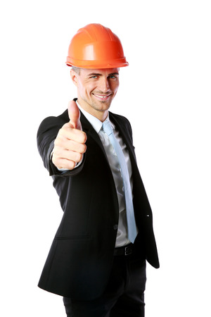 Businessman in helmet giving thumbs up over white background photo