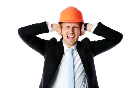 Businessman in helmet covering his ears over white background photo