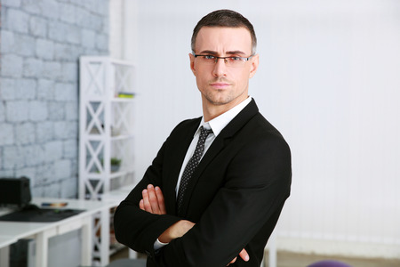 Confident businessman with arms folded standing in office photo