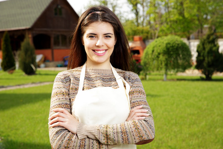 Happy woman standing with arms folded in folded in garden photo