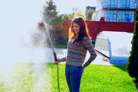 Portrait of a cheerful woman is watering a garden photo