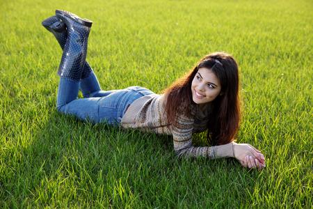芝生の上に横たわる幸せな女の肖像