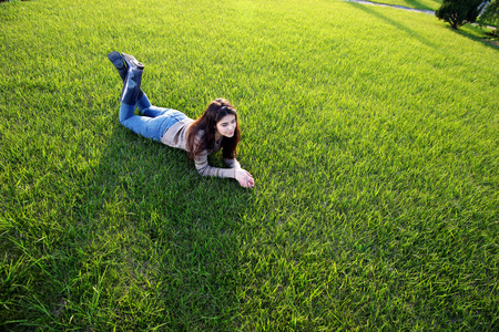 Portrait of a happy woman lying on green grass Imagens