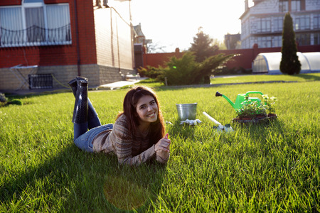 Portrait of a happy woman lying on green grass Stock Photo