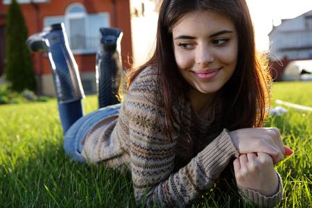 思いやりのある女性に横たわって、芝生と離れて見て 写真素材