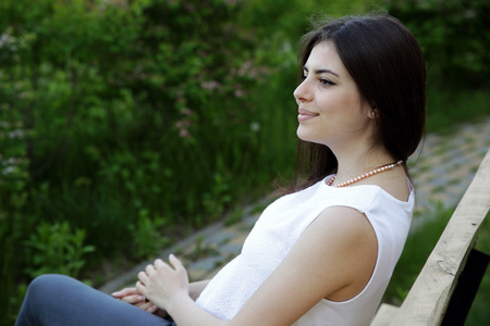 brunett: Young happy woman sitting on the bench in park