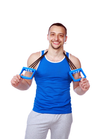 Happy muscular sportsman with expanders over white background photo