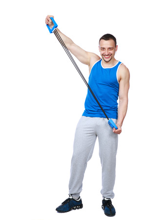 Full length portrait of a muscular sportsman with expanders over white background photo