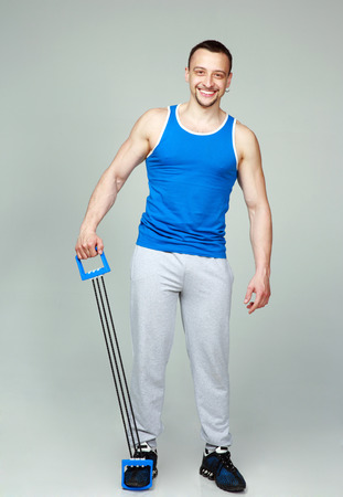 Happy muscular sportsman with expanders on gray background photo