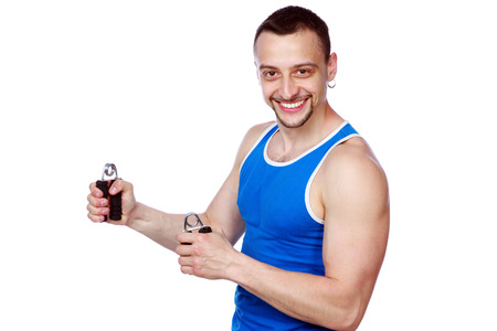 Smiling muscular sportsman with expanders over white background photo