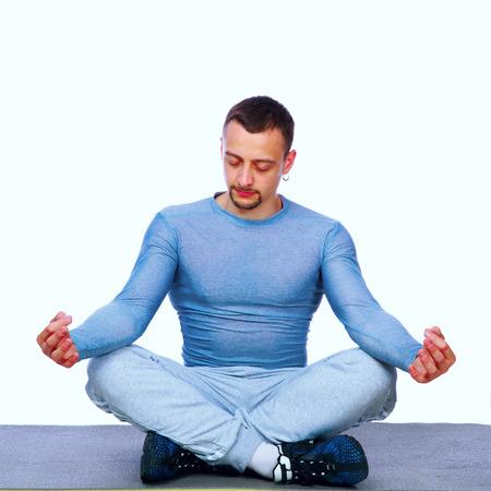 dhyana: Sportivo Concentrato seduto nella posizione del loto sul grigio Archivio Fotografico