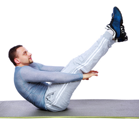Muscular man exercising on exercise mat over white  photo