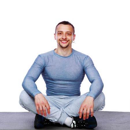 dhyana: Happy sportsman sitting in the lotus position over white background