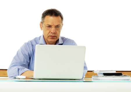 50 yrs: Portrait of a middle aged caucasian man looking at his laptop computer.