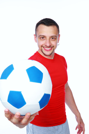 Happy sportive man holding soccer ball over white background photo