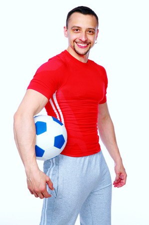 Sportive man holding soccer ball over white background photo