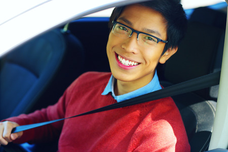 Young asian man fastening seat belt photo