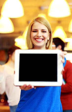 Smiling student showing tablet computer screen photo