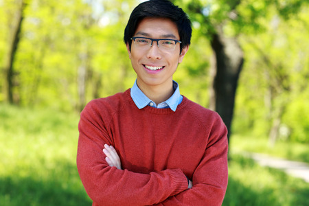 Cheerful asian young man standing with arms folded in a park photo