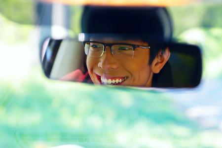 retrovisor: Retrato de un hombre asi�tico feliz se sienta en el asiento del conductor y se ve en el espejo retrovisor