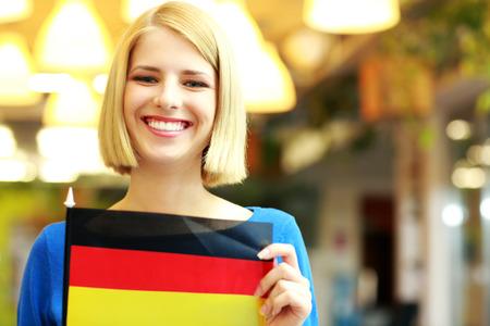 Cheerful blonde girl holding flag of Germani photo