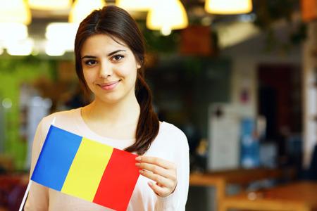 Gelukkig vrouwelijke student die de vlag van Roemenië