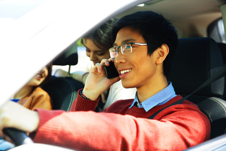 Young cheerful man driving car and speaking on mobile phone photo