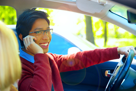 Young happy man driving car and speaking on mobile phone photo