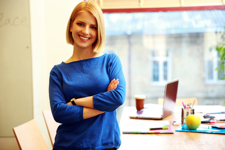 Young smiling woman standing in office photo