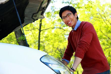 Side view portrait of a young asian man checking his car engine photo